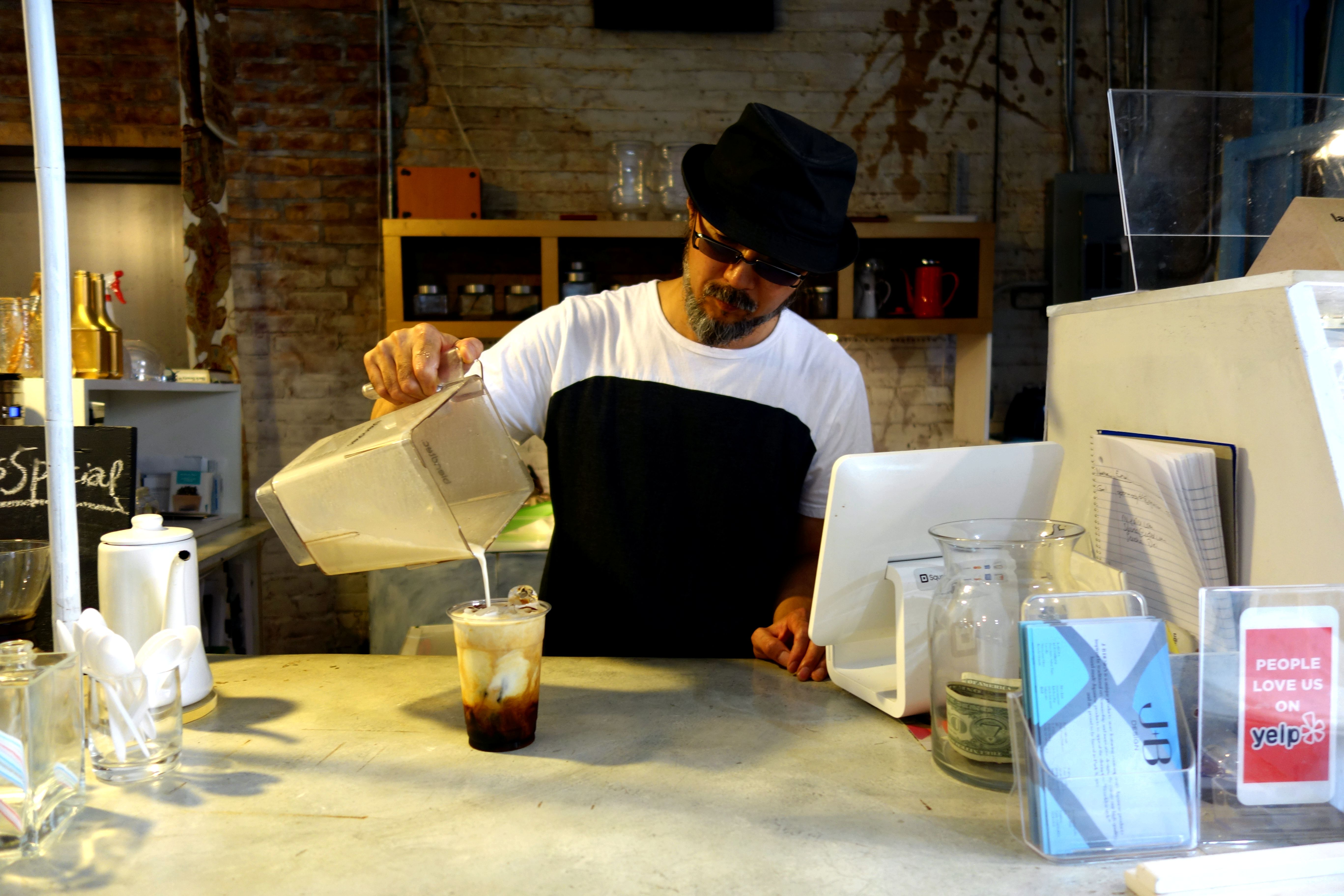 Fumio Tashiro pouring banana milk on coffee